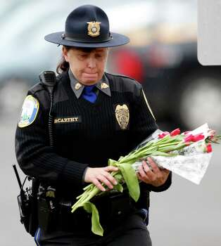 Newtown Police Officer Maryhelen McCarthy places flowers at a makeshift memorial outside St. Rose of Lima Roman Catholic Church, Sunday, Dec. 16, 2012, in Newtown, Conn. On Friday, a gunman allegedly killed his mother at their home and then opened fire inside the Sandy Hook Elementary School, killing 26 people, including 20 children. (AP Photo/Julio Cortez) Photo: Julio Cortez, Associated Press / Associated Press