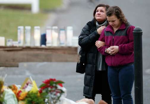 People pay respects by a makeshift memorial outside of St. Rose of Lima Roman Catholic Church between Mass services, Sunday, Dec. 16, 2012, in Newtown, Conn. On Friday, a gunman allegedly killed his mother at their home and then opened fire inside the Sandy Hook Elementary School, killing 26 people, including 20 children. (AP Photo/Julio Cortez) Photo: Julio Cortez, Associated Press / Associated Press