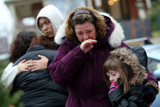 Mourners grieve at one of the makeshift memorials for victims of the Sandy Hook Elementary School shooting, Sunday, Dec. 16, 2012, in Newtown, Conn. On Friday, a gunman allegedly killed his mother at their home and then opened fire inside the school, killing 26 people, including 20 children. (AP Photo/Mary Altaffer) Photo: Mary Altaffer, Associated Press / Associated Press