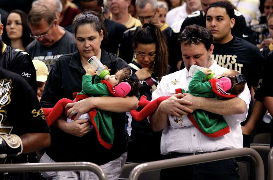 Fans pause during a moment of silence to honor 20 children and 6 adults killed Friday in a shooting rampage at Sandy Hook Elementary School in Newtown, Conn., in the first half of an NFL football game between the New Orleans Saints and the Tampa Bay Buccaneers at the Mercedes-Benz Superdome in New Orleans, Sunday, Dec. 16, 2012.  A gunman walked into Sandy Hook Elementary School in Newtown, Conn. Friday and opened fire, killing 26 people.  (AP Photo/Bill Haber) Photo: Bill Haber, Associated Press / Associated Press