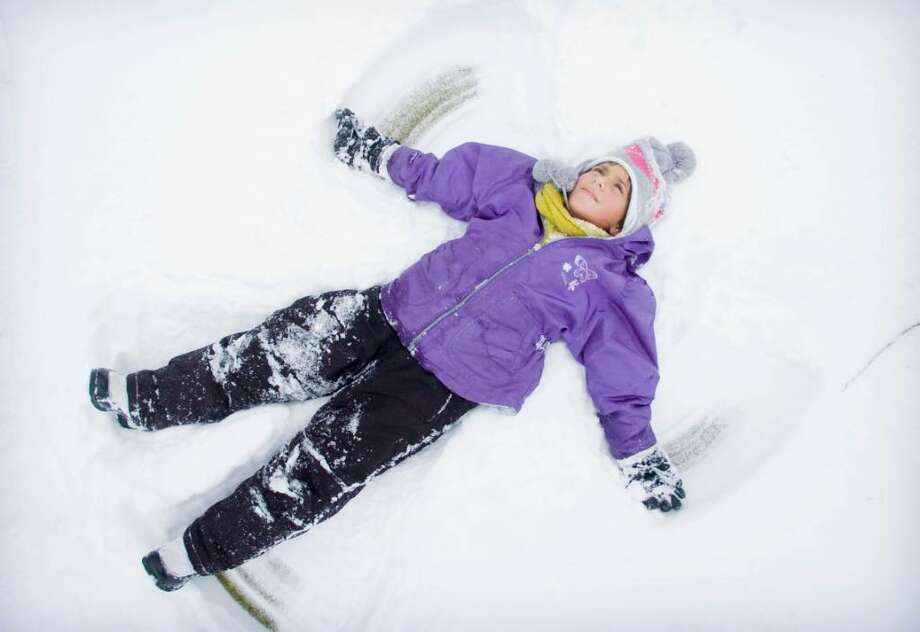Bella Franchina, 9, who is visiting from snowless San Diego, makes a snow angel at E. Gaynor Brennan Municipal Golf Couse after the snow storm in Stamford, Conn. on Sunday, Dec. 20, 2009. Photo: Chris Preovolos / Stamford Advocate