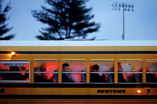 People arrive on a school bus at Newtown High School for a memorial vigil attended by President Barack Obama for the victims of the Sandy Hook Elementary School shooting, Sunday, Dec. 16, 2012, in Newtown, Conn. A gunman walked into Sandy Hook Elementary School in Newtown Friday and opened fire, killing 26 people, including 20 children. (AP Photo/David Goldman) Photo: David Goldman, Associated Press / Associated Press