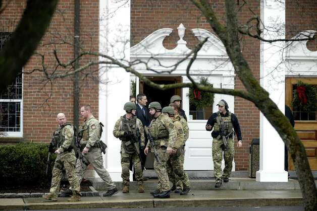 A swat team walks out of St. Rose of Lima Roman Catholic Church while responding to a bomb threat, Sunday, Dec. 16, 2012, in Newtown, Conn. Worshippers hurriedly left the church Sunday, not far from where a gunman opened fire Friday inside the Sandy Hook Elementary School in Newtown. (AP Photo/David Goldman) Photo: David Goldman, Associated Press / Associated Press