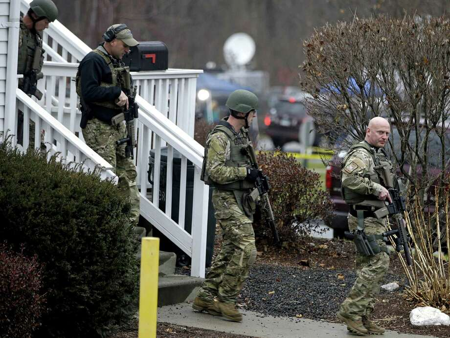 A swat team walks out of the rectory of St. Rose of Lima Roman Catholic Church while responding to a bomb threat, Sunday, Dec. 16, 2012, in Newtown, Conn. Worshippers hurriedly left the church Sunday, not far from where a gunman opened fire Friday inside the Sandy Hook Elementary School in Newtown. (AP Photo/David Goldman) Photo: David Goldman, Associated Press / Associated Press