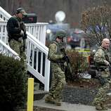 A swat team walks out of the rectory of St. Rose of Lima Roman Catholic Church while responding to a bomb threat, Sunday, Dec. 16, 2012, in Newtown, Conn. Worshippers hurriedly left the church Sunday, not far from where a gunman opened fire Friday inside the Sandy Hook Elementary School in Newtown. (AP Photo/David Goldman)