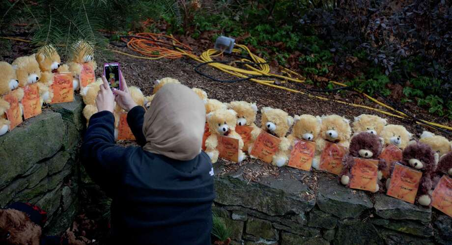 A mourner takes a picture of 26 teddy bears, each representing a victim of the Sandy Hook Elementary School shooting, at a sidewalk memorial, Sunday, Dec. 16, 2012, in Newtown, Conn. A gunman walked into Sandy Hook Elementary School in Newtown Friday and opened fire, killing 26 people, including 20 children. (AP Photo/David Goldman) Photo: David Goldman, Associated Press / Associated Press