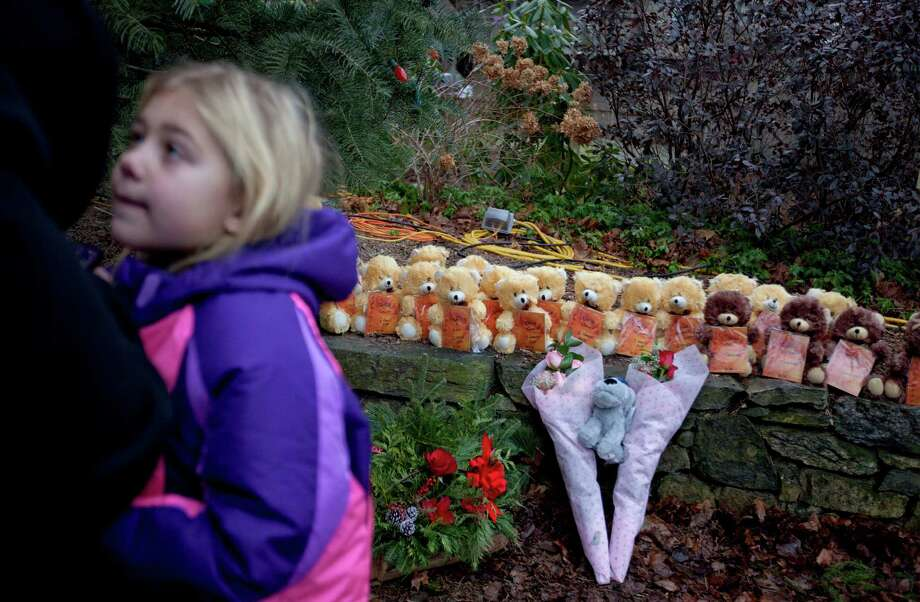 Ava Staiti, 7, of New Milford, Conn., looks up at her mother Emily Staiti, while visiting a sidewalk memorial with 26 teddy bears, each representing a victim of the Sandy Hook Elementary School shooting, Sunday, Dec. 16, 2012, in Newtown, Conn. A gunman walked into Sandy Hook Elementary School in Newtown Friday and opened fire, killing 26 people, including 20 children. (AP Photo/David Goldman) Photo: David Goldman, Associated Press / Associated Press