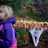 Ava Staiti, 7, of New Milford, Conn., looks up at her mother Emily Staiti, while visiting a sidewalk memorial with 26 teddy bears, each representing a victim of the Sandy Hook Elementary School shooting, Sunday, Dec. 16, 2012, in Newtown, Conn. A gunman walked into Sandy Hook Elementary School in Newtown Friday and opened fire, killing 26 people, including 20 children. (AP Photo/David Goldman)