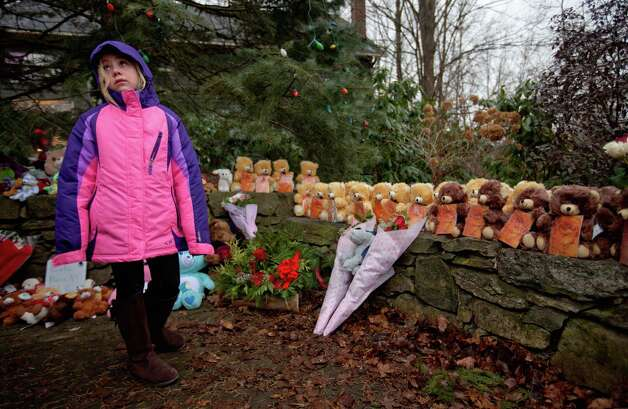 Ava Staiti, 7, of New Milford, Conn., looks up at her mother Emily Staiti, not pictured, while visiting a sidewalk memorial with 26 teddy bears, each representing a victim of the Sandy Hook Elementary School shooting, Sunday, Dec. 16, 2012, in Newtown, Conn. A gunman walked into Sandy Hook Elementary School in Newtown Friday and opened fire, killing 26 people, including 20 children. (AP Photo/David Goldman) Photo: David Goldman, Associated Press / Associated Press