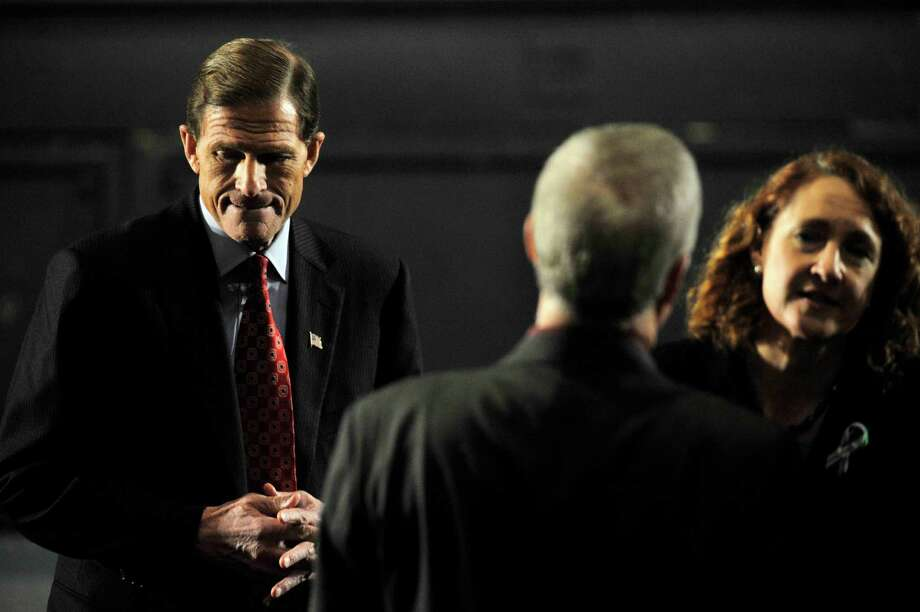 Sen. Richard Blumenthal, left, stands alone as U.S. Congresswoman-elect Elizabeth Esty greets people before President Barack Obama speaks in the Newtown High School auditorium on Sunday, Dec. 16, 2012. Photo: Jason Rearick / The News-Times