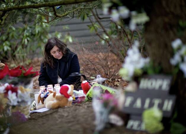 Dilma Steiner, of Newtown, Conn., visits a sidewalk memorial for the Sandy Hook Elementary School shooting victims, Sunday, Dec. 16, 2012, in Newtown, Conn. A gunman walked into Sandy Hook Elementary School in Newtown Friday and opened fire, killing 26 people, including 20 children. (AP Photo/David Goldman) Photo: David Goldman, Associated Press / Associated Press