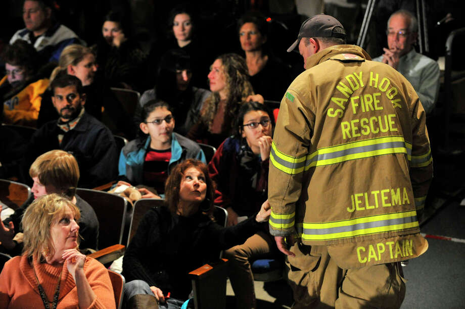 A Sandy Hook firefighter talks to people waiting for President Barack Obama to speak in the Newtown High School auditorium on Sunday, Dec. 16, 2012. Photo: Jason Rearick / The News-Times