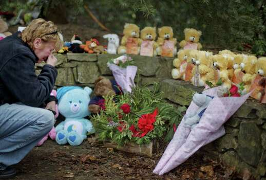 Cheryl Girardi, of Middletown, Conn., kneels beside 26 teddy bears, each representing a victim of the Sandy Hook Elementary School shooting, at a sidewalk memorial, Sunday, Dec. 16, 2012, in Newtown, Conn. A gunman walked into Sandy Hook Elementary School in Newtown Friday and opened fire, killing 26 people, including 20 children.(AP Photo/David Goldman) Photo: David Goldman, Associated Press / Associated Press