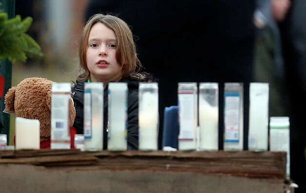 A young girl holding a teddy bear looks at a makeshift memorial outside of St. Rose of Lima Roman Catholic Church, Sunday, Dec. 16, 2012, in Newtown, Conn. On Friday, a gunman allegedly killed his mother at their home and then opened fire inside the Sandy Hook Elementary School in Newtown, killing 26 people, including 20 children.(AP Photo/Julio Cortez) Photo: Julio Cortez, Associated Press / Associated Press
