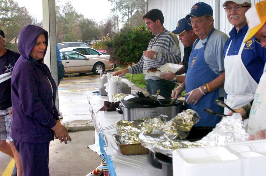 Beaumont resident Helen Doga waits as Knights of Columbus volunteers assemble her order. Despite the rain, many came out to enjoy some barbecue chicken and Zummo links in support of the organization's chicken dinner, benefiting the Empty Stocking Fund. Photo: Sarah Moore