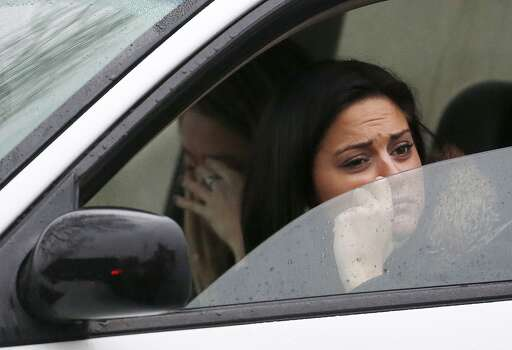 Women react while waiting in a vehicle to drive away from St. Rose of Lima Roman Catholic Church as officials respond to a bomb threat, Sunday, Dec. 16, 2012, in Newtown, Conn. Worshippers hurriedly left the church Sunday, not far from where a gunman opened fire Friday inside the Sandy Hook Elementary School in Newtown. (AP Photo/Julio Cortez) Photo: Julio Cortez, Associated Press / Associated Press
