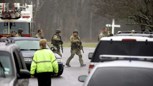 A swat team responds to a bomb threat at St. Rose of Lima Roman Catholic Church, Sunday, Dec. 16, 2012, in Newtown, Conn. Worshippers hurriedly left the church Sunday, not far from where a gunman opened fire Friday inside the Sandy Hook Elementary School in Newtown. (AP Photo/David Goldman) Photo: David Goldman, Associated Press / Associated Press