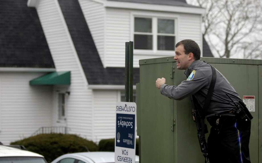 A police officer takes up a position behind the rectory of the St. Rose of Lima Roman Catholic Church in response to a call of a bomb threat, Sunday, Dec. 16, 2012, in Newtown, Conn. (AP Photo/David Goldman) Photo: David Goldman, Associated Press / Associated Press