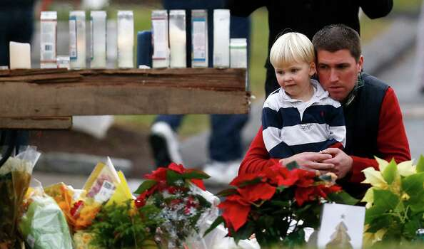 A man holds a child while paying respects to shooting victims at a makeshift memorial outside of St. Rose of Lima Roman Catholic Church, Sunday, Dec. 16, 2012, in Newtown, Conn. On Friday, a gunman killed his mother at their home and then opened fire inside the Sandy Hook Elementary School in Newtown, killing 26 people, including 20 children.(AP Photo/Julio Cortez) Photo: Julio Cortez, Associated Press / Associated Press