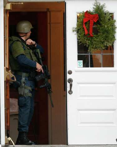 A Connecticut State Police officer wearing SWAT gear stands on the doorway at  St. Rose of Lima Roman Catholic Church while responding to a bomb threat, Sunday, Dec. 16, 2012, in Newtown, Conn. Worshippers hurriedly left the church on Sunday, saying they were told there was a bomb threat, not far from the elementary school where 20 kids and six adults were massacred on Friday. The all-clear was given after an hour in which armed police in SWAT gear searched the church and adjacent buildings. (AP Photo/Julio Cortez) Photo: Julio Cortez, Associated Press / Associated Press