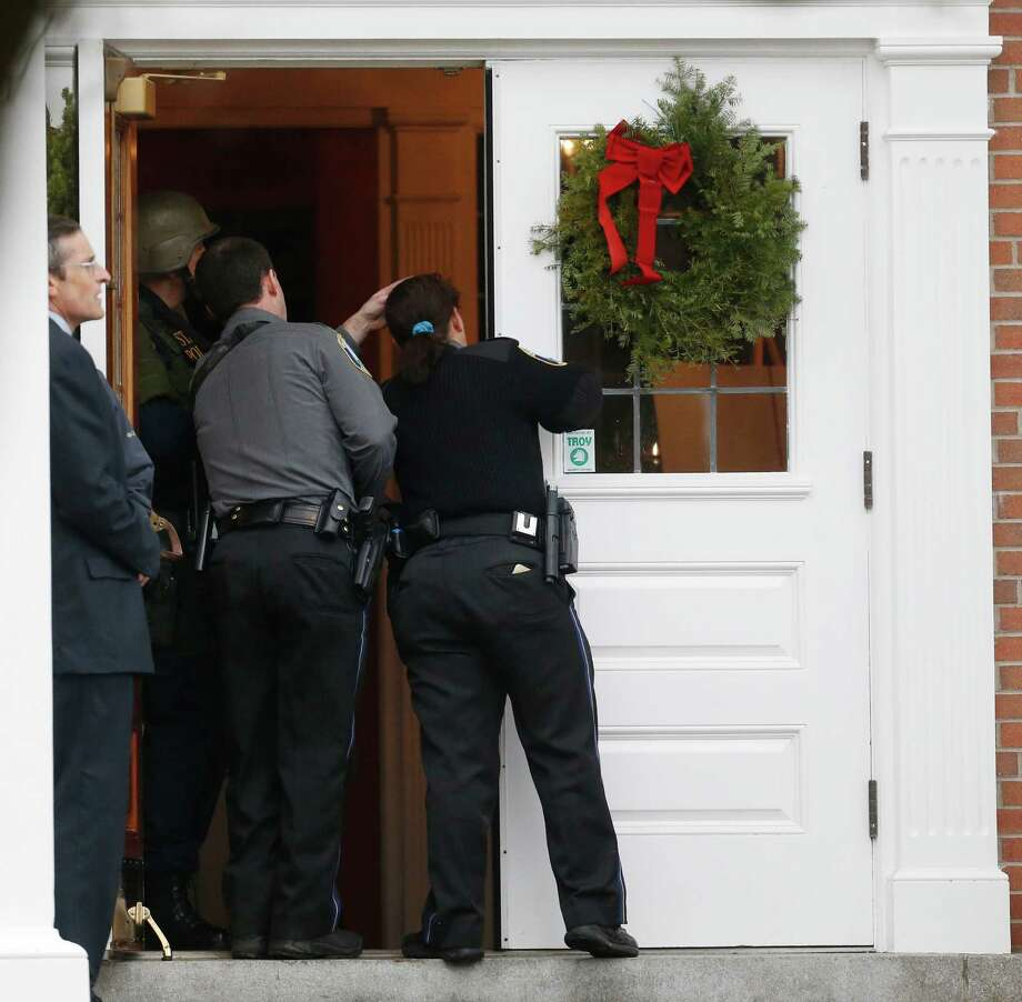 Newtown Police Officer Maryhelen McCarthy, right, looks into St. Rose of Lima Roman Catholic Church with other officials while responding to a threat, Sunday, Dec. 16, 2012, in Newtown, Conn. Worshippers hurriedly left the church on Sunday, saying they were told there was a bomb threat, not far from the elementary school where 20 kids and six adults were massacred on Friday. The all-clear was given after an hour in which armed police in SWAT gear searched the church and adjacent buildings. (AP Photo/Julio Cortez) Photo: Julio Cortez, Associated Press / Associated Press