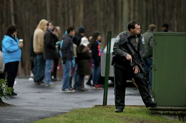 A police officer takes up a position behind the rectory of the St. Rose of Lima Roman Catholic Church in response to a bomb threat as onlookers watch from a Starbucks parking lot, Sunday, Dec. 16, 2012, in Newtown, Conn. Worshippers hurriedly left the church Sunday, not far from the elementary school where 20 kids and six adults were massacred on Friday. (AP Photo/David Goldman) Photo: David Goldman, Associated Press / Associated Press