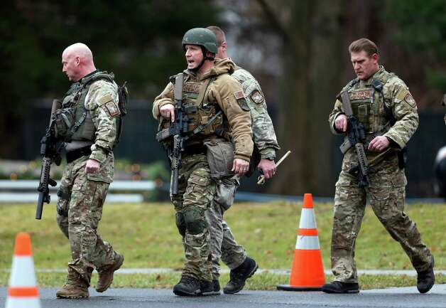 Connecticut State Police officers respond to a bomb threat outside of St. Rose of Lima Roman Catholic Church, Sunday, Dec. 16, 2012, in Newtown, Conn. Worshippers hurriedly left the church Sunday, not far from where a gunman opened fire Friday inside the Sandy Hook Elementary School in Newtown. (AP Photo/Julio Cortez) Photo: Julio Cortez, Associated Press / Associated Press