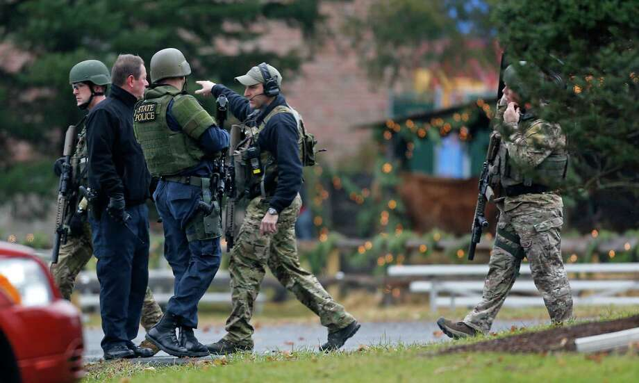 A Connecticut State Police tactical team searches the area around St. Rose of Lima Catholic Church while responding to a bomb threat, Sunday, Dec. 16, 2012, in Newtown, Conn. Worshippers hurriedly left the church Sunday, not far from where a gunman opened fire Friday inside the Sandy Hook Elementary School in Newtown. (AP Photo/Charles Krupa) Photo: Charles Krupa, Associated Press / Associated Press