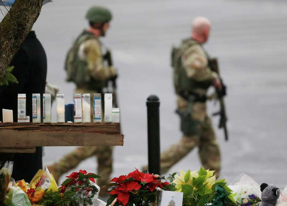 Candles and flowers are seen on a makeshift memorial as officials walk by while responding to a bomb threat, Sunday, Dec. 16, 2012, in Newtown, Conn. Worshippers hurriedly left the church Sunday, not far from where a gunman opened fire Friday inside the Sandy Hook Elementary School in Newtown. (AP Photo/Julio Cortez) Photo: Julio Cortez, Associated Press / Associated Press