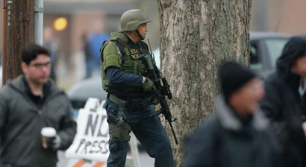 A Conn. State Police tactical team officer takes cover behind a tree as the area around St. Rose of Lima Catholic Church is searched in Newtown, Conn., Sunday, Dec. 16, 2012 after a there was a bomb threat. A gunman opened fire at Sandy Hook Elementary School in the town, killing 26 people, including 20 children before killing himself on Friday. (AP Photo/Charles Krupa) Photo: Charles Krupa, Associated Press / Associated Press
