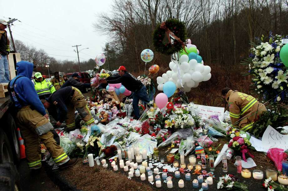 Firefighters and other volunteers reorganize a memorial for shooting victims near Sandy Hook Elementary School before erecting a shelter over it, Sunday, Dec. 16, 2012 in Newtown, Conn.  A gunman walked into Sandy Hook Elementary School in Newtown Friday and opened fire, killing 26 people, including 20 children. (AP Photo/Jason DeCrow) Photo: Jason DeCrow, Associated Press / Associated Press