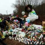 Firefighters and other volunteers reorganize a memorial for shooting victims near Sandy Hook Elementary School before erecting a shelter over it, Sunday, Dec. 16, 2012 in Newtown, Conn.  A gunman walked into Sandy Hook Elementary School in Newtown Friday and opened fire, killing 26 people, including 20 children. (AP Photo/Jason DeCrow)