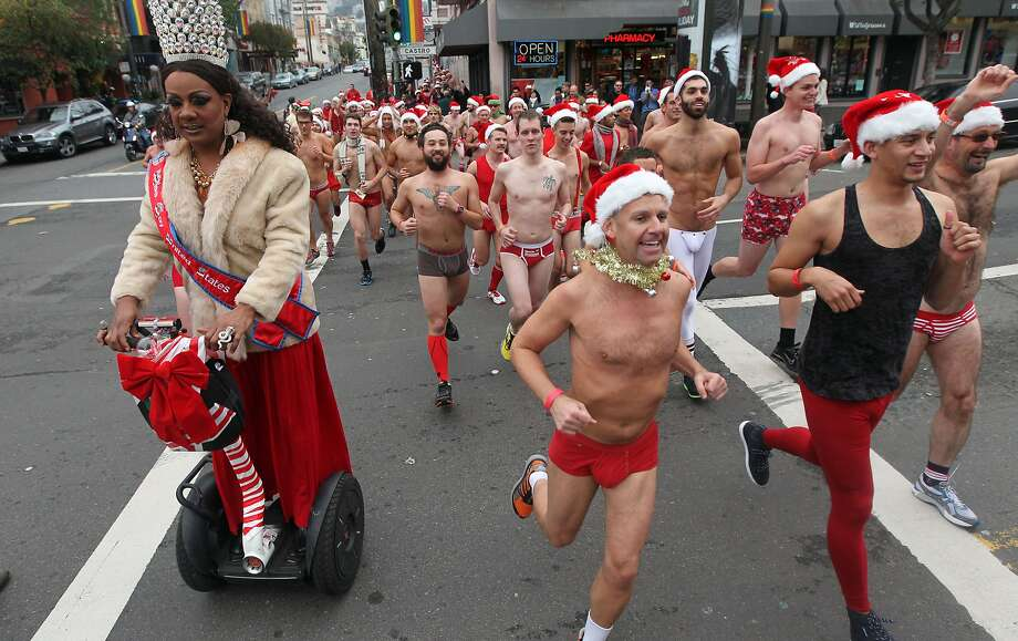 Runners cross Castro Street in the annual Santa Skivvies Run Sunday, Dec. 16, 2012. Four hundred volunteers and joggers took part, raising $43,000 for the AIDS Foundation. Runners started at the Lookout Bar on Market Street then ran through the Castro District taking a spontaneous route, much to the delight of onlookers. Photo: Lance Iversen, The Chronicle