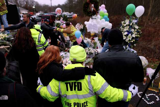 Onlookers embrace as firefighters and other volunteers reorganize a memorial for shooting victims near Sandy Hook Elementary School before erecting a shelter over it, Sunday, Dec. 16, 2012 in Newtown, Conn.  A gunman walked into Sandy Hook Elementary School in Newtown on Friday and opened fire, killing 26 people, including 20 children. (AP Photo/Jason DeCrow) Photo: Jason DeCrow, Associated Press / Associated Press