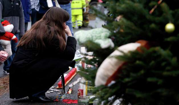 A mourner pays her respects at a memorial for shooting victims near Sandy Hook Elementary School, Sunday, Dec. 16, 2012 in Newtown, Conn.  A gunman walked into Sandy Hook Elementary School in Newtown on Friday and opened fire, killing 26 people, including 20 children. (AP Photo/Jason DeCrow) Photo: Jason DeCrow, Associated Press / Associated Press