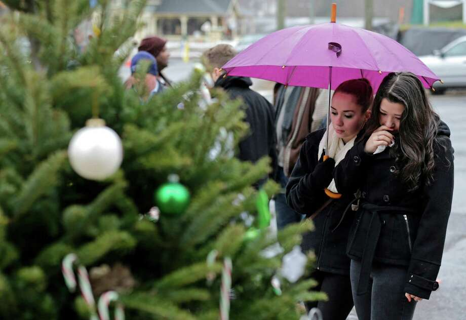 Two girls pause at the site of a makeshift memorial for school shooting victims at the village of Sandy Hook in Newtown, Conn., Sunday, Dec. 16, 2012. A gunman opened fire at Sandy Hook Elementary School in the town, killing 26 people, including 20 children before killing himself on Friday. (AP Photo/Charles Krupa) Photo: Charles Krupa, Associated Press / Associated Press