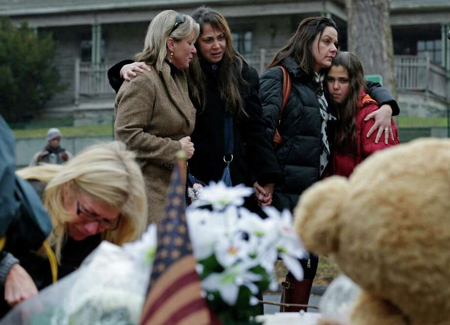 Women embrace at the site of a makeshift memorial for school shooting victims at the village of Sandy Hook in Newtown, Conn., Sunday, Dec. 16, 2012. A gunman opened fire at Sandy Hook Elementary School in the town, killing 26 people, including 20 children before killing himself on Friday. (AP Photo/Charles Krupa) Photo: Charles Krupa, Associated Press / Associated Press