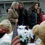 Women embrace at the site of a makeshift memorial for school shooting victims at the village of Sandy Hook in Newtown, Conn., Sunday, Dec. 16, 2012. A gunman opened fire at Sandy Hook Elementary School in the town, killing 26 people, including 20 children before killing himself on Friday. (AP Photo/Charles Krupa)