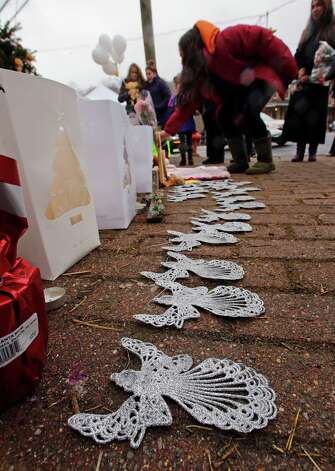 A woman lays flowers at the site of a makeshift memorial for school shooting victims at the village of Sandy Hook in Newtown, Conn., Sunday, Dec. 16, 2012. A gunman opened fire at Sandy Hook Elementary School in the town, killing 26 people, including 20 children before killing himself on Friday. (AP Photo/Charles Krupa) Photo: Charles Krupa, Associated Press / Associated Press