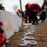 A woman lays flowers at the site of a makeshift memorial for school shooting victims at the village of Sandy Hook in Newtown, Conn., Sunday, Dec. 16, 2012. A gunman opened fire at Sandy Hook Elementary School in the town, killing 26 people, including 20 children before killing himself on Friday. (AP Photo/Charles Krupa)