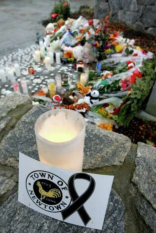 A note rests next to a candle near a makeshift memorial outside of St. Rose of Lima Roman Catholic Church following a Sunday Mass, Sunday, Dec. 16, 2012, in Newtown, Conn. On Friday, a gunman allegedly killed his mother at their home and then opened fire inside the Sandy Hook Elementary School in Newtown, killing 26 people, including 20 children. (AP Photo/Julio Cortez) Photo: Julio Cortez, Associated Press / Associated Press