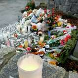 A note rests next to a candle near a makeshift memorial outside of St. Rose of Lima Roman Catholic Church following a Sunday Mass, Sunday, Dec. 16, 2012, in Newtown, Conn. On Friday, a gunman allegedly killed his mother at their home and then opened fire inside the Sandy Hook Elementary School in Newtown, killing 26 people, including 20 children. (AP Photo/Julio Cortez)