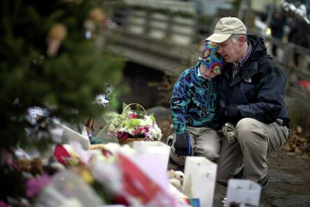 David Freedman, right, kneels with his son Zachary, 9, both of Newtown, Conn., as they visit a sidewalk memorial for the Sandy Hook Elementary School shooting victims, Sunday, Dec. 16, 2012, in Newtown, Conn. A gunman walked into Sandy Hook Elementary School in Newtown Friday and opened fire, killing 26 people, including 20 children. (AP Photo/David Goldman) Photo: David Goldman, Associated Press / Associated Press