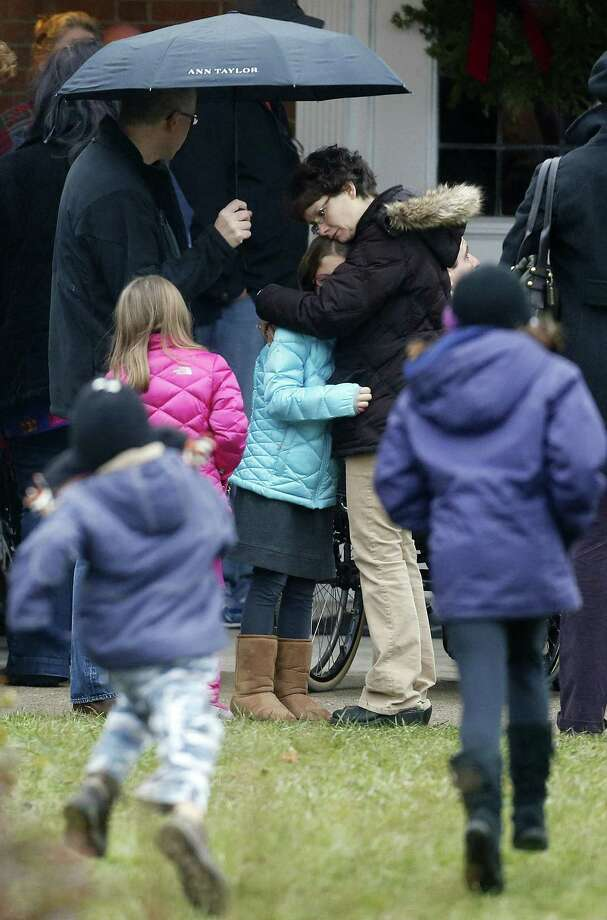 A woman embraces a child as children run outside of St. Rose of Lima Roman Catholic Church before a Sunday mass service, Sunday, Dec. 16, 2012, in Newtown, Conn. On Friday, a gunman allegedly killed his mother at their home and then opened fire inside the Sandy Hook Elementary School in Newtown, killing 26 people, including 20 children. (AP Photo/Julio Cortez) Photo: Julio Cortez, Associated Press / Associated Press