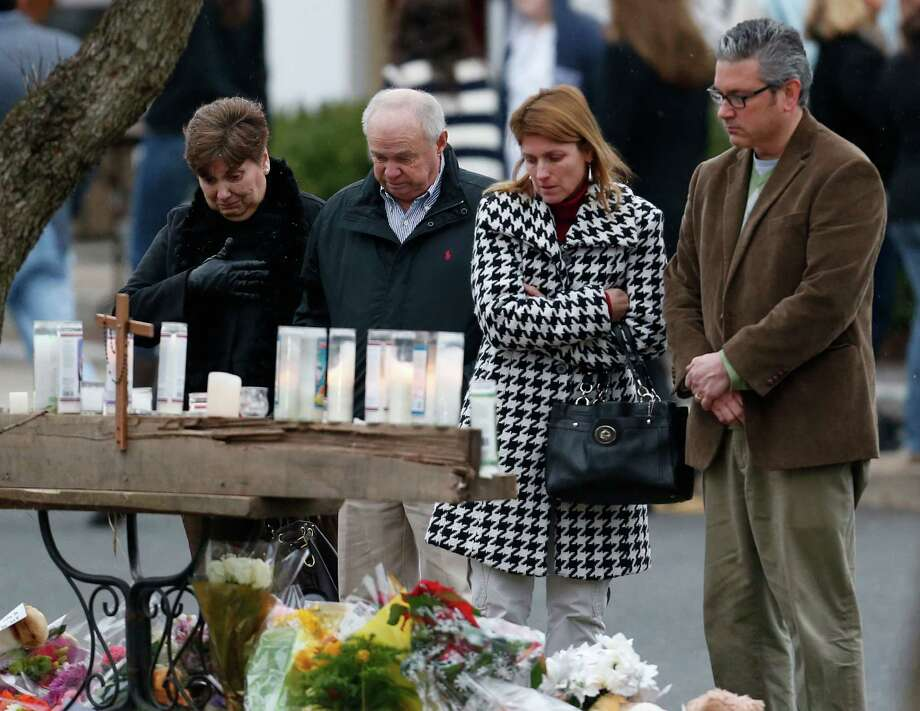 People pay respects at a makeshift memorial outside of St. Rose of Lima Roman Catholic Church between Mass services, Sunday, Dec. 16, 2012, in Newtown, Conn. On Friday, a gunman allegedly killed his mother at their home and then opened fire inside the Sandy Hook Elementary School in Newtown, killing 26 people, including 20 children. (AP Photo/Julio Cortez) Photo: Julio Cortez, Associated Press / Associated Press