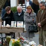People pay respects at a makeshift memorial outside of St. Rose of Lima Roman Catholic Church between Mass services, Sunday, Dec. 16, 2012, in Newtown, Conn. On Friday, a gunman allegedly killed his mother at their home and then opened fire inside the Sandy Hook Elementary School in Newtown, killing 26 people, including 20 children. (AP Photo/Julio Cortez)