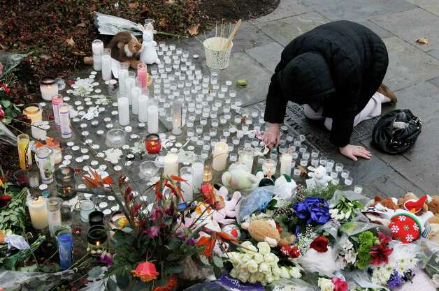 A woman pays respects at a memorial outside of St. Rose of Lima Roman Catholic Church, Sunday, Dec. 16, 2012, in Newtown, Conn. On Friday, a gunman allegedly killed his mother at their home and then opened fire inside the Sandy Hook Elementary School in Newtown, killing 26 people, including 20 children. (AP Photo/Julio Cortez) Photo: Julio Cortez, Associated Press / Associated Press