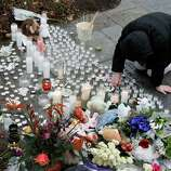 A woman pays respects at a memorial outside of St. Rose of Lima Roman Catholic Church, Sunday, Dec. 16, 2012, in Newtown, Conn. On Friday, a gunman allegedly killed his mother at their home and then opened fire inside the Sandy Hook Elementary School in Newtown, killing 26 people, including 20 children. (AP Photo/Julio Cortez)