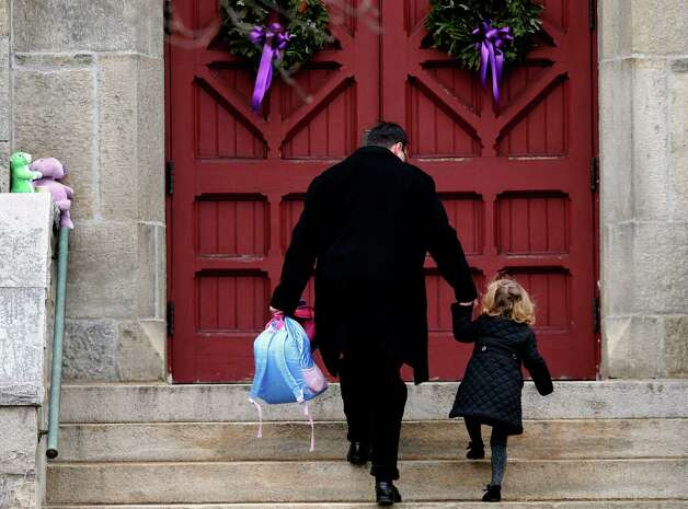 A man helps a young girl up the stairs while carrying her backpack as they arrive for services at Trinity Church, Sunday, Dec. 16, 2012 in Newtown, Conn.  A gunman walked into Sandy Hook Elementary School in Newtown Friday and opened fire, killing 26 people, including 20 children. (AP Photo/Jason DeCrow) Photo: Jason DeCrow, Associated Press / Associated Press