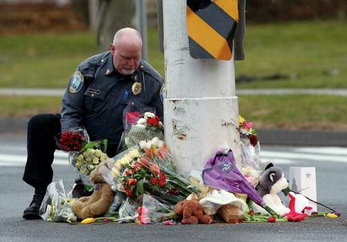A police officer relocates items from a memorial to shooting victims that had been left in the middle of a busy intersection, Sunday, Dec. 16, 2012 in Newtown, Conn.  A gunman walked into Sandy Hook Elementary School in Newtown Friday and opened fire, killing 26 people, including 20 children.  The items were taken to nearby Saint Rose of Lima Roman Catholic Church. (AP Photo/Jason DeCrow) Photo: Jason DeCrow, Associated Press / Associated Press
